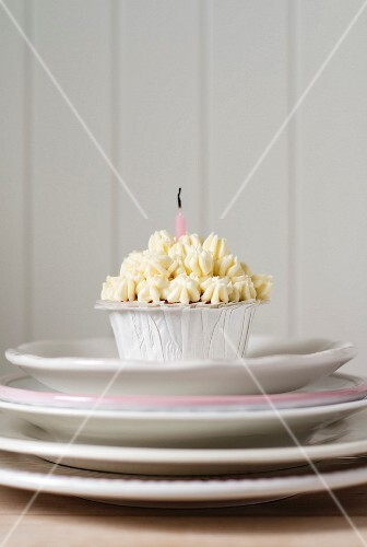 A birthday cupcake with a white cream topping an a blown-out candle