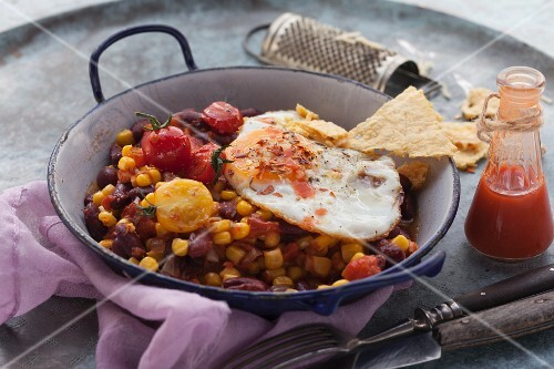 A fried egg on kidney bean and sweet corn hash (Tex-Mex)