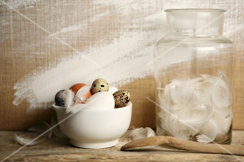 Various eggs in a bowl next to a jar of white feathers