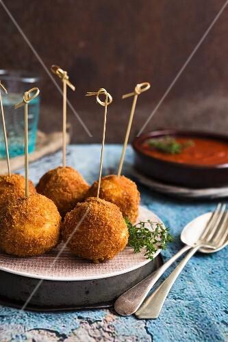 Arancini on sticks with tomato sauce