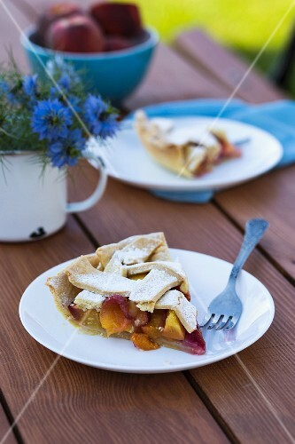 Two slices of peach pie on a wooden table in a garden