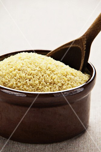Bulgur wheat in a ceramic bowl with a wooden spoon