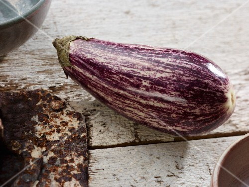 A striped aubergine on old, white floor boards