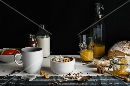 A breakfast table laid with milk, cereals, orange juice, bread, honey and grapefruit