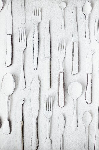 Various items of cutlery dusted with flour (seen from above)