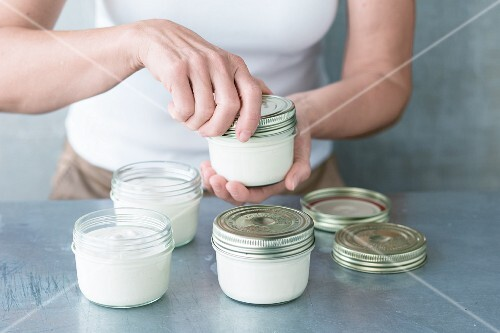 Screw-top jars of cashew nut and coconut yoghurt being closed
