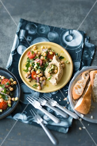 Chickpea salad with cherry tomatoes and parsley on hummus