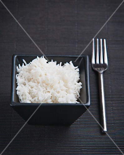 Cooked rice in a black dish on a black surface