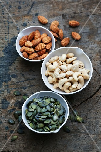 Bowls of almonds, cashew nuts and pumpkin seeds