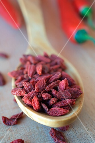 Dried goji berries on a wooden spoon