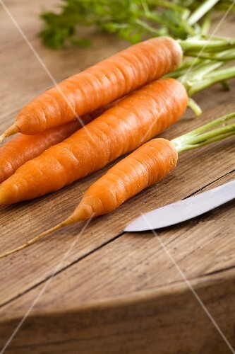 Fresh carrots on a wooden table with a knife