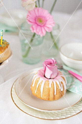 A mini iced Bundt cake decorated with roses
