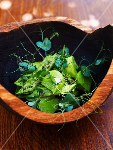 Kohlrabi baked in salt dough and grilled broad beans with shoots