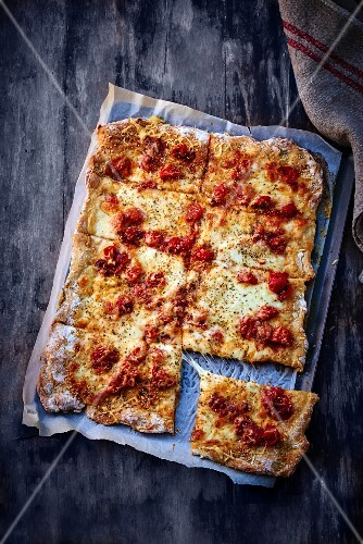A sliced cheese and tomato tray bake pizza
