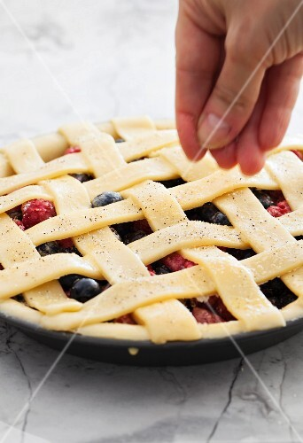 An unbaked berry pie being sprinkled with vanilla sugar
