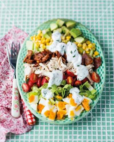 A mixed vegetable salad with chicken, bacon, eggs and a yoghurt dressing