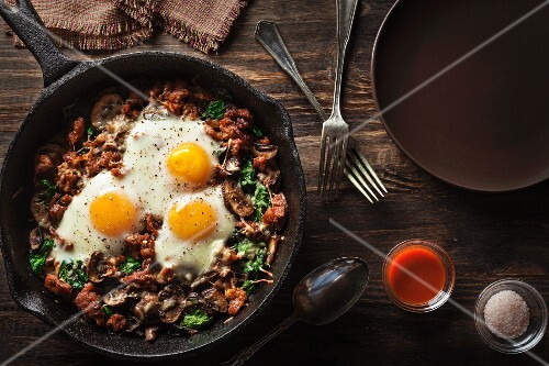 Fried mushrooms with spinach, sausage and fried eggs (seen from above)