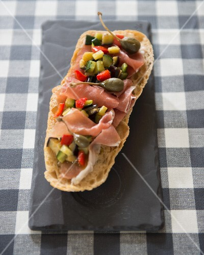 A slice of toasted bread with raw ham, vegetables and capers (Spain)
