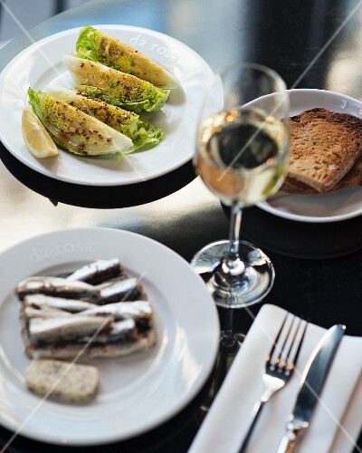 Various tapas (sardines and lettuce) with wine and bread