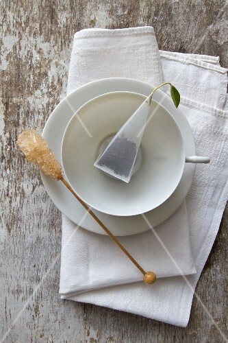 A cup of tea with a tea bag and rock candy stick on a saucer
