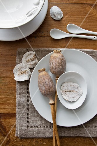 A place setting with dried poppy seed pods