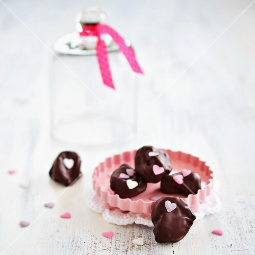 Plums in chocolate decorated with sugar hearts