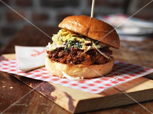 A chilli burger on a wooden board