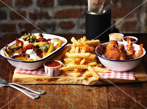 Pulled pork-based dishes and snacks on a wooden board