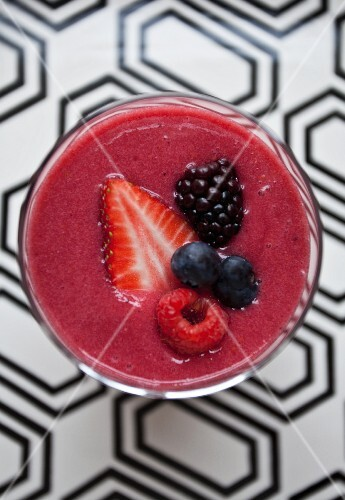 A berry smoothie in a glass on a patterned surface (seen from above)
