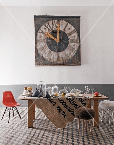 Eclectic interior with tiled floor, table set with glassware, Eames chair and old church tower clock on wall