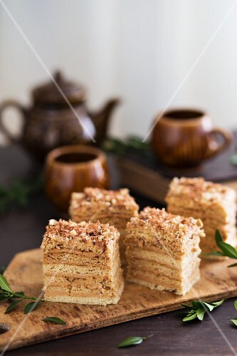 Slices of honey layer cake with walnuts on a rustic wooden board with teacups and a teapot in the background