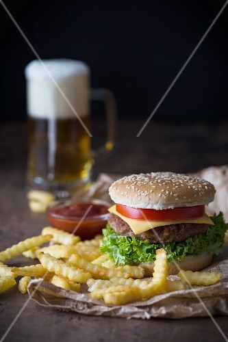 A homemade cheeseburger with chips, tomato sauce and a glass of beer