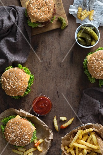 Homemade burgers with chips, tomato sauce and gherkins (seen from above)