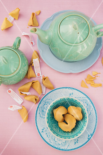Pastellblaues Teegedeck, Teekanne und aufgebrochene Glückskekse auf rosa Tischdecke
