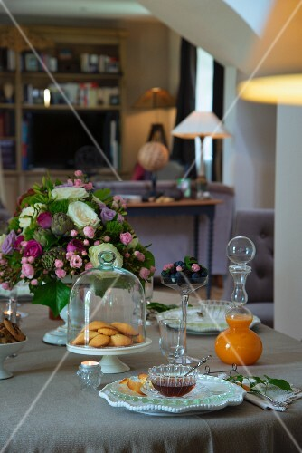 Set table with pastries under glass cover, vase of flowers and glass carafe of juice