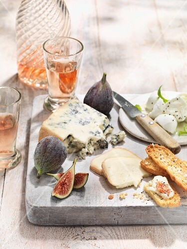 A cheese platter with figs, grilled bread and rose wine