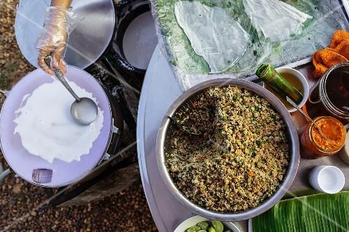 Vietnamese rice flour rolls with pork filling being prepared at a market (Vientiane, Laos)