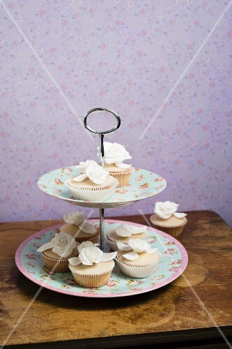 Cupcakes decorated with sugar flowers on a cake stand