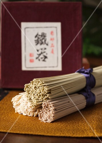 Three bundles of soba and udon noodles on a golden mat