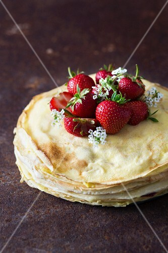 A stack of crepes with fresh strawberries