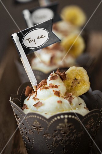 Chocolate cupcakes with a banana topping in a paper case with a flag