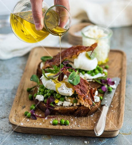 An open sandwich being drizzled with olive oil