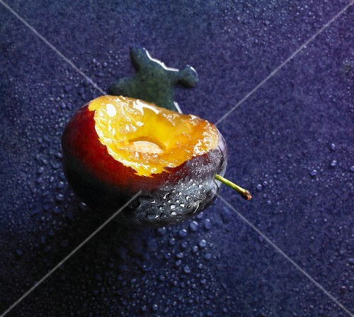 A freshly washed plum with a bite taken out