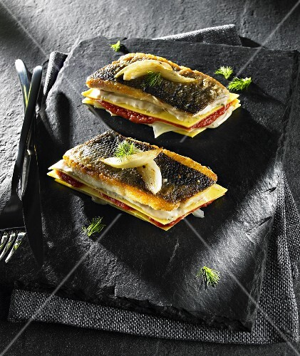 Fish lasagne with tomatoes and a Bechamel sauce on a stone platter