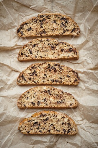 A row of biscotti on a piece of brown paper (seen from above)