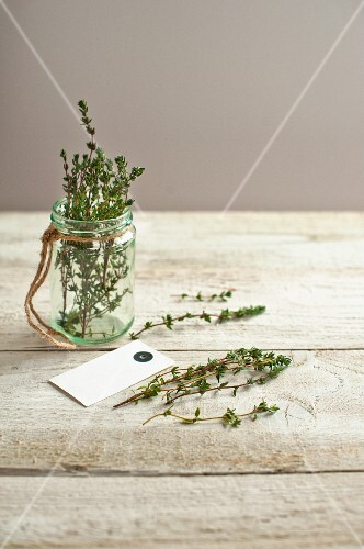 A jar of thyme herb on a light wooden surface