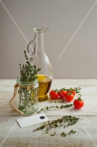 A bottle of olive oil, thyme and cherry tomatoes on a light wooden surface