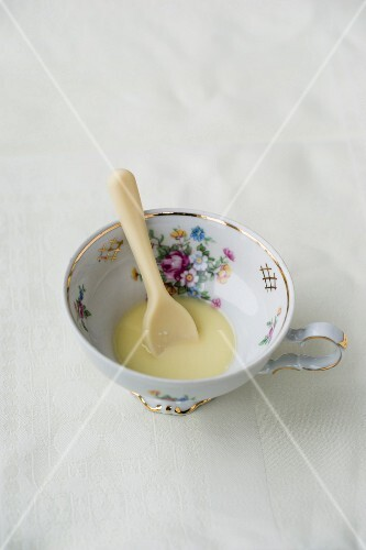 A white chocolate spoon dissolving in hot milk
