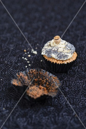 A mini cupcake with a poppyseed and vanilla topping