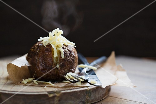 A steaming baked potato with cheese on a piece of baking paper